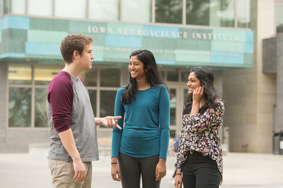 three undergraduate researchers conversing outside facility