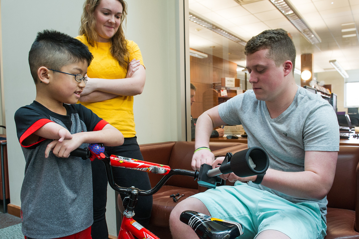 engineering students prepare an assistive device for a boy's bicycle