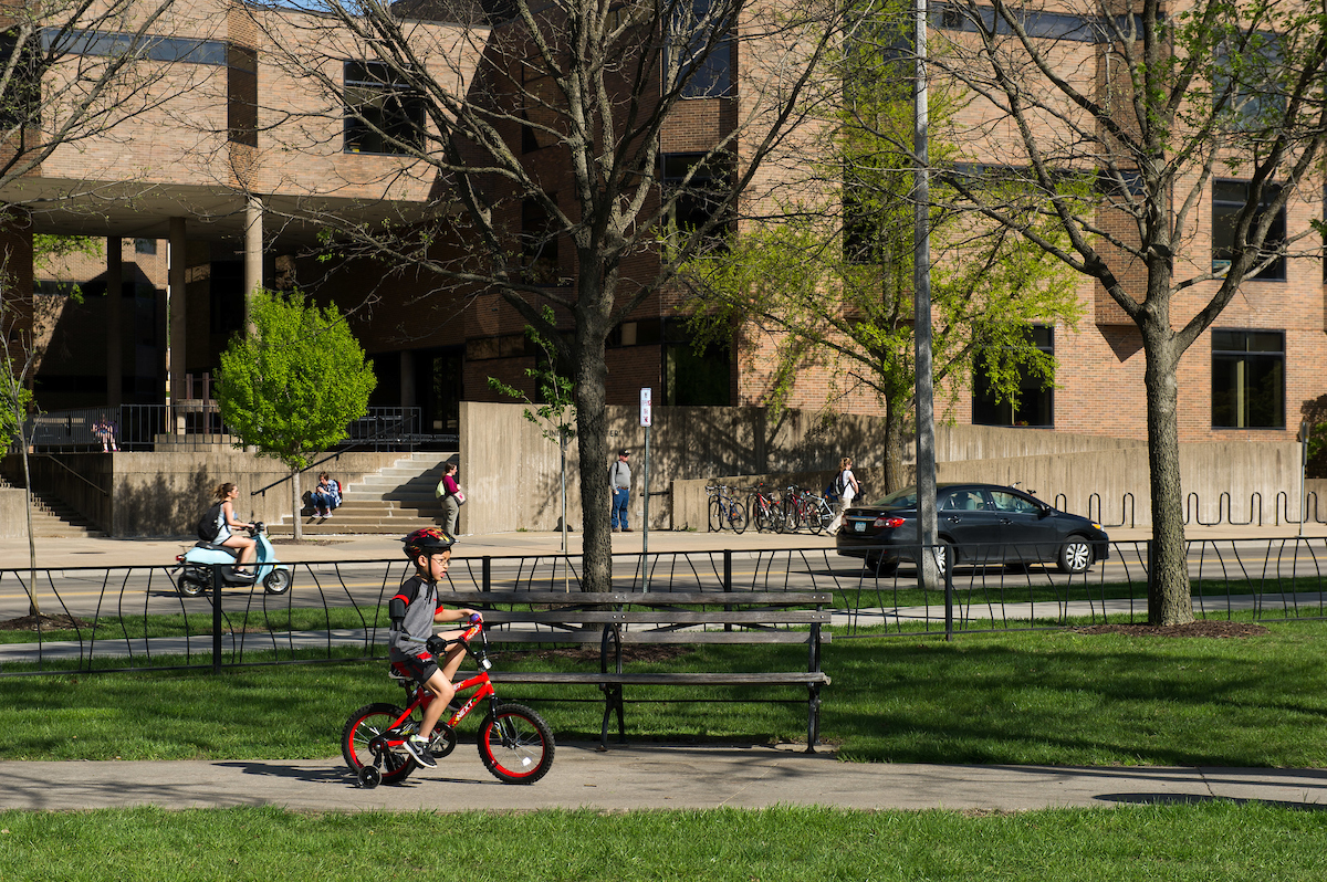 boy riding bicycle on campus using assistive device