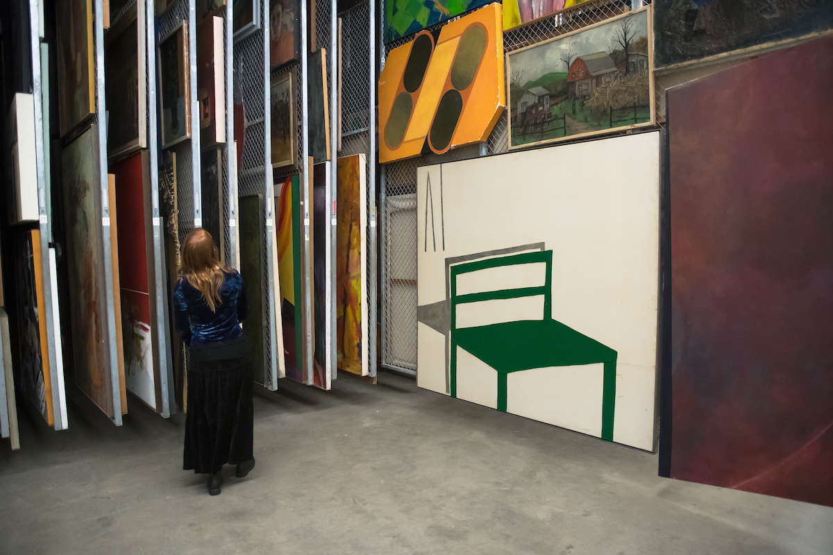 curator moving racks in the thesis rental gallery at the university of iowa