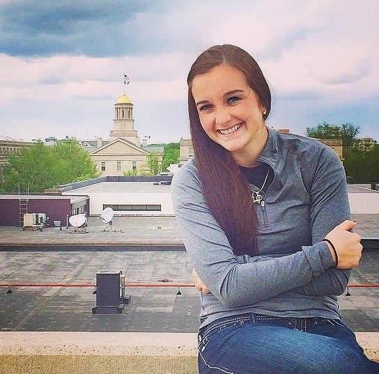 student posing on campus with old capitol museum in background