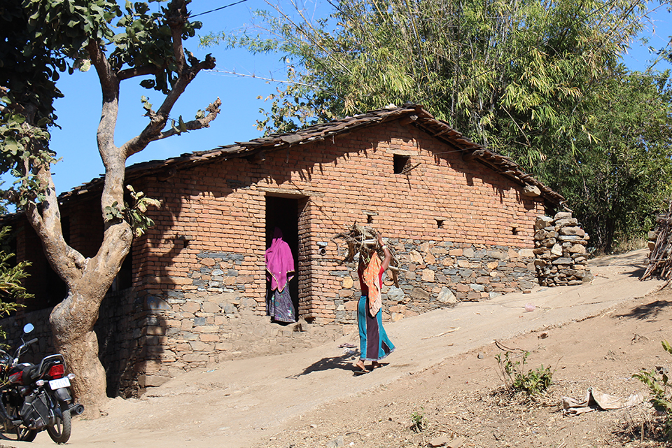 women carrying wood into home
