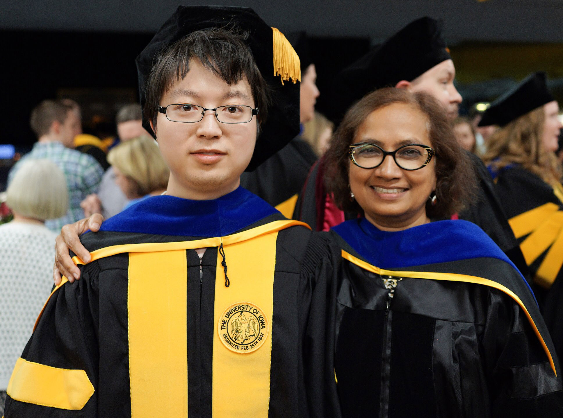 man and woman posing at commencement ceremony