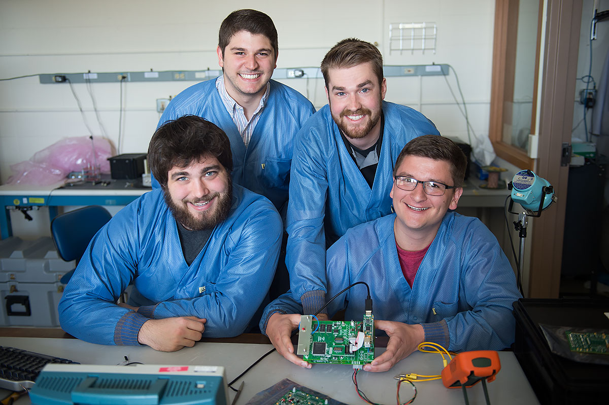 Bryan Senchuk, Kevin Klosterman (top), Tyler Dunkel, and Patrick Maloney (bottom) show off the circuit board and microprocessor they built to reenact Van Allen's experiment. Photo by Tim Schoon.