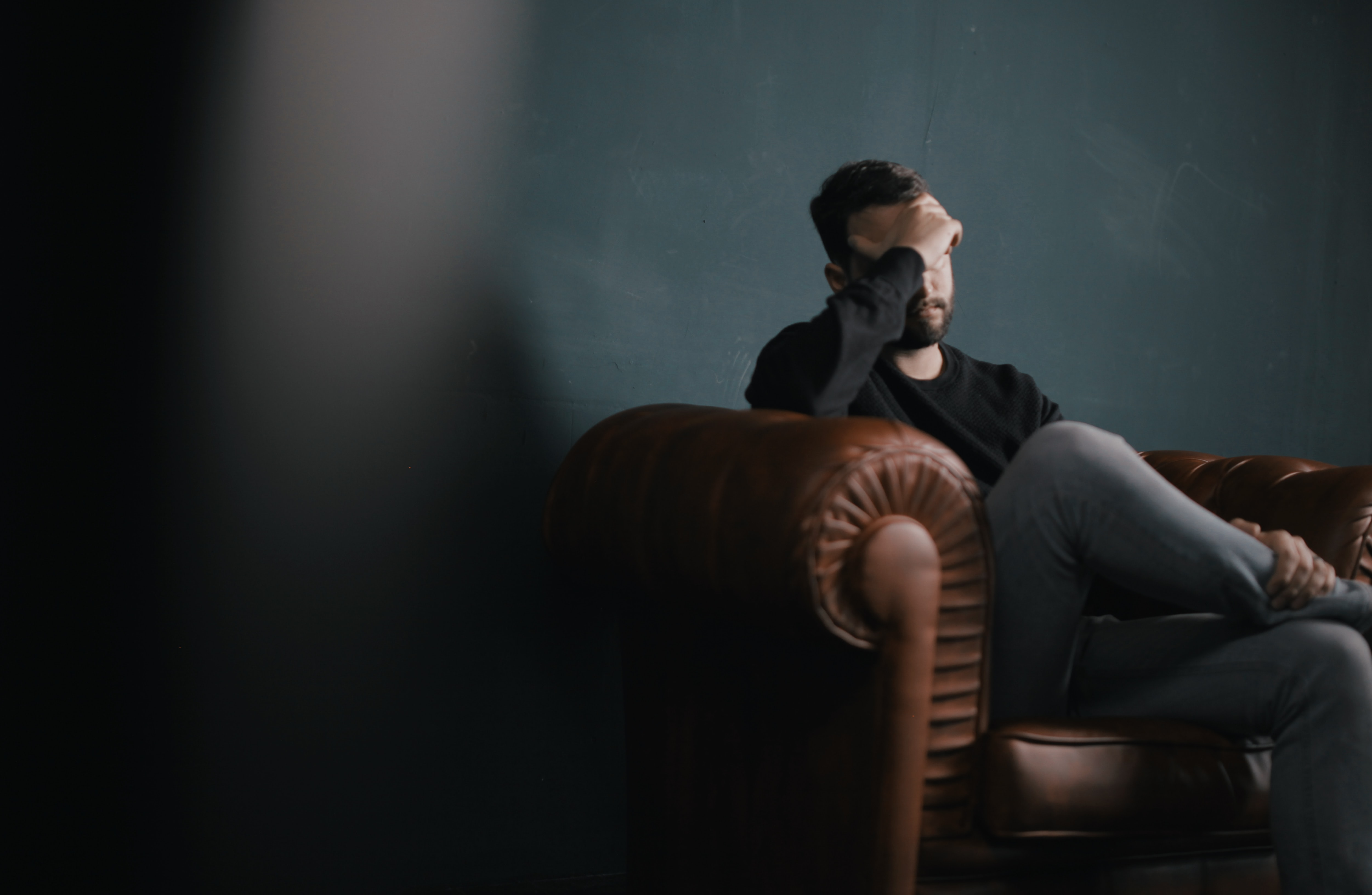 man on leather couch holding head