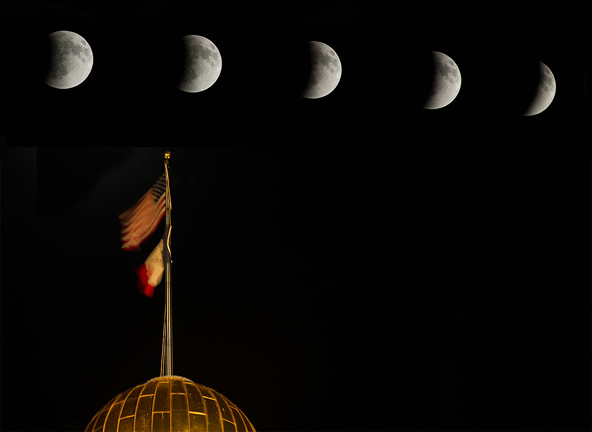 The moon in various stages of its eclipse appears in the sky above the Old Capitol on Tuesday morning.